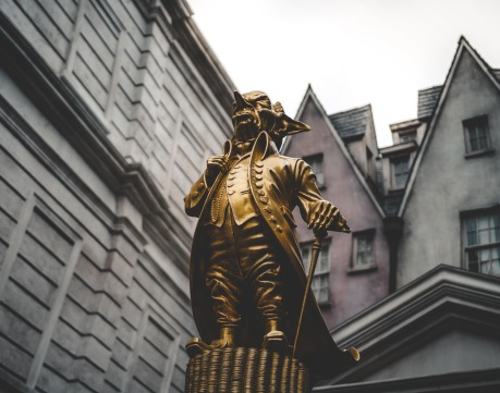 Gold statue of man holding gold statue