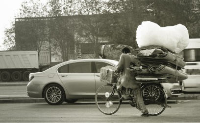 Grayscale photo of man and woman riding bicycle on road