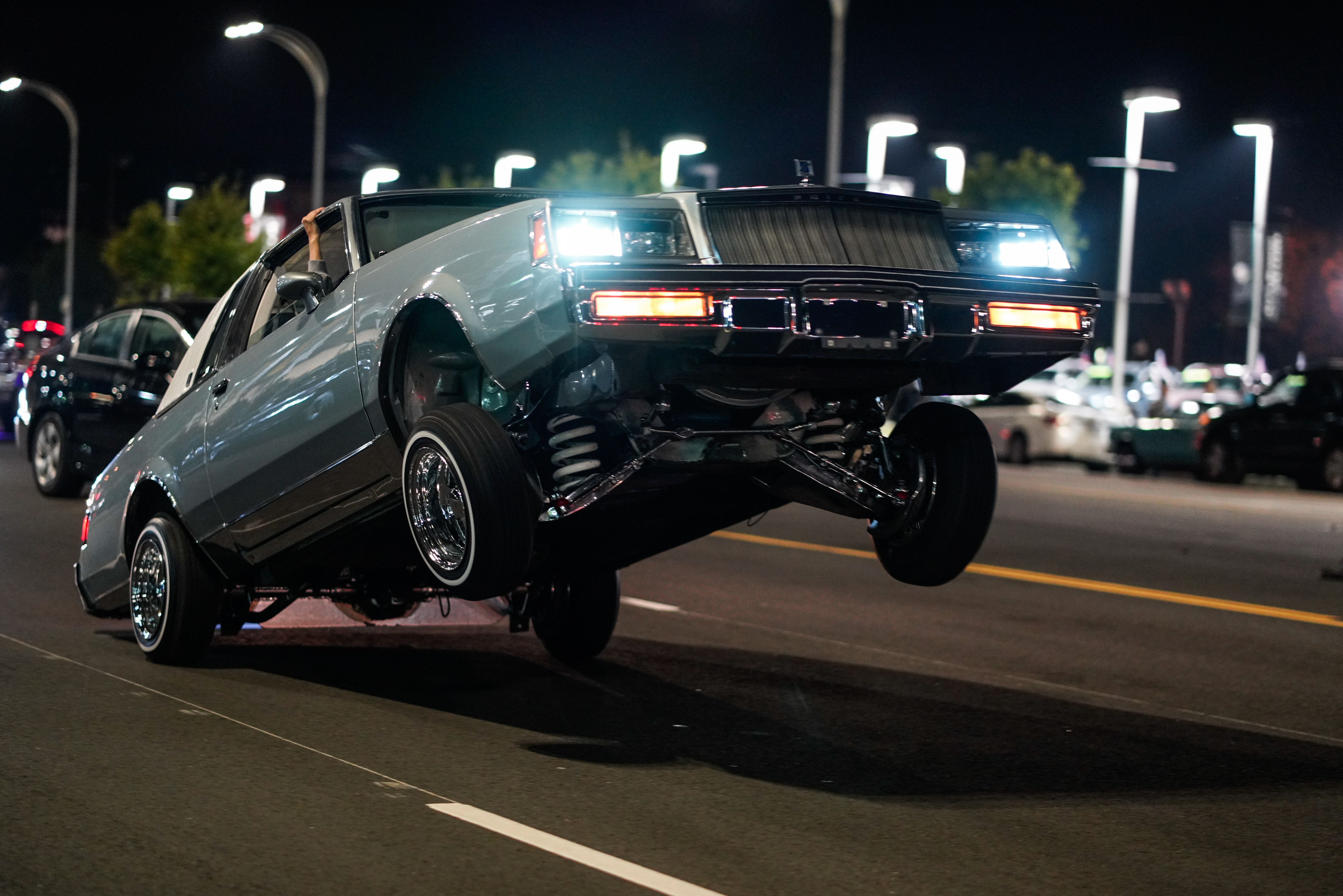 blue muscle car jumping in the road